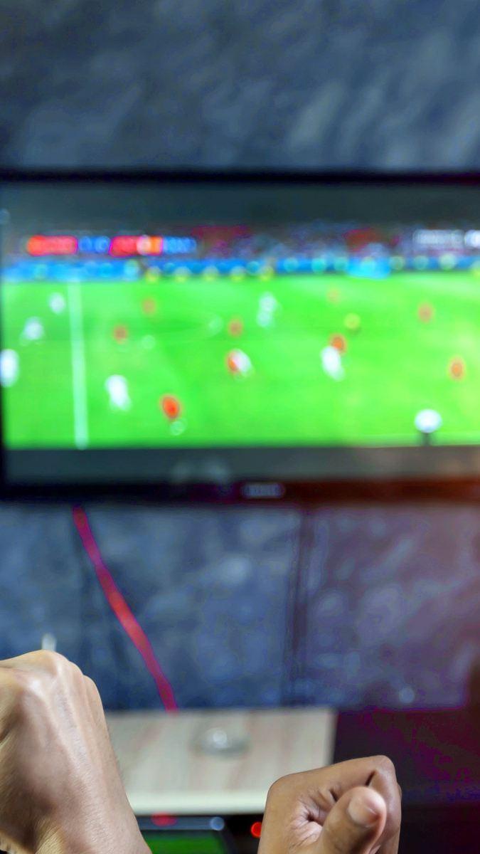 Menschen schauen auf einem Fernseher ein Fußballspiel