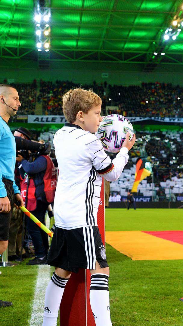 Ein Kind trägt den Spielball