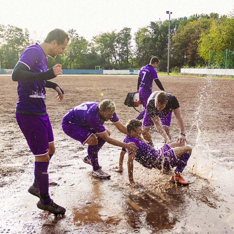 Fußballspieler auf einem nassen Schotterplatz