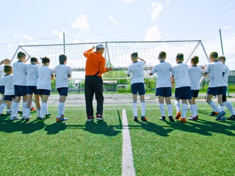 Kinder stellen ein Fußballtor auf