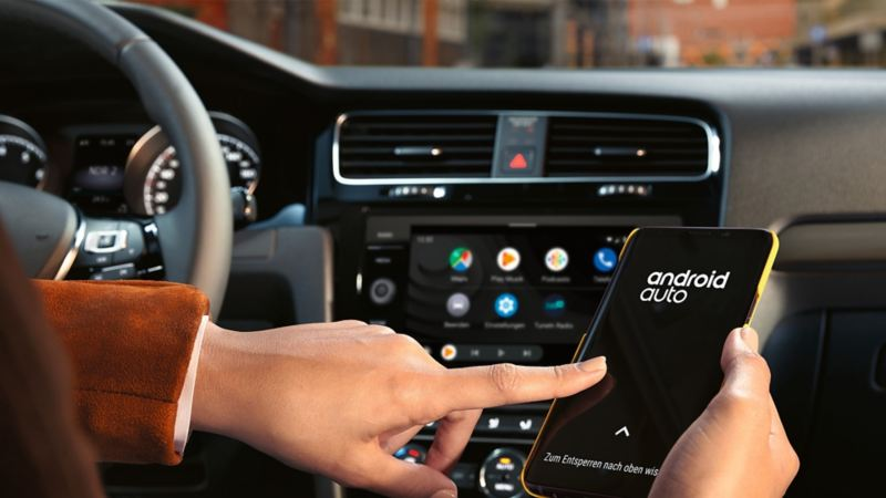 A person selecting Android Auto app on their smartphone