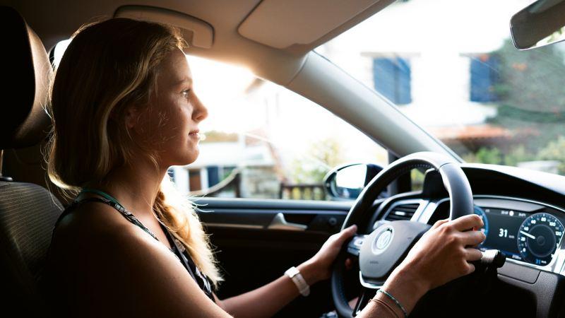 A woman sitting inside an e-Golf car