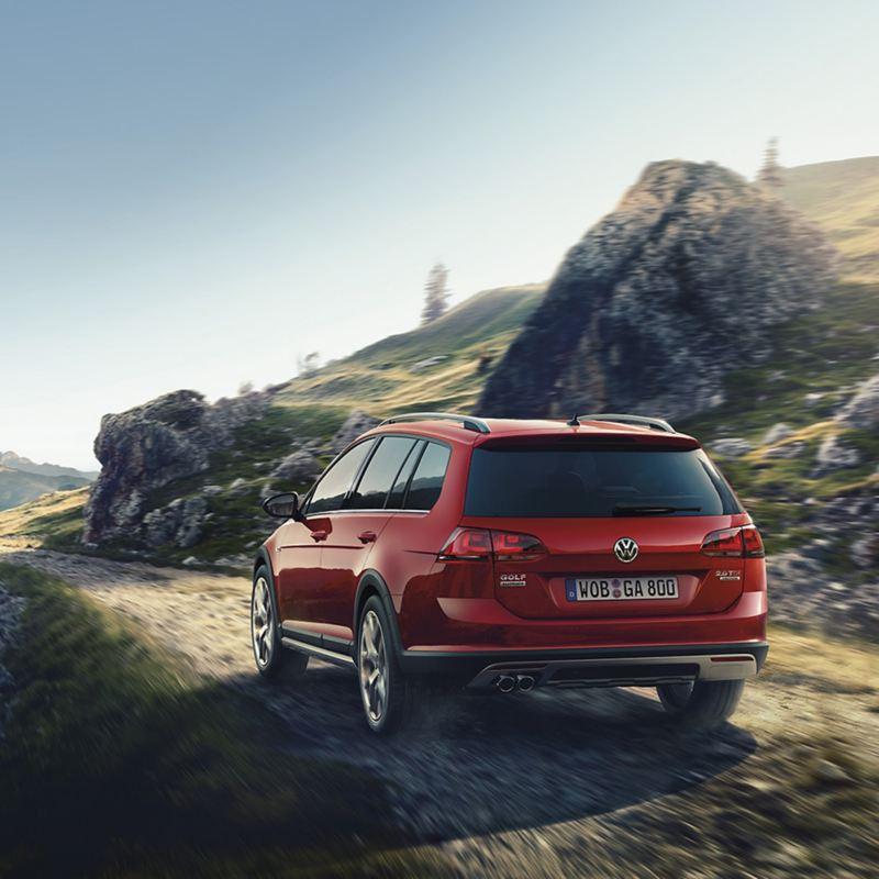 Volkswagen bil åker på kuperad väg i bergstrakter