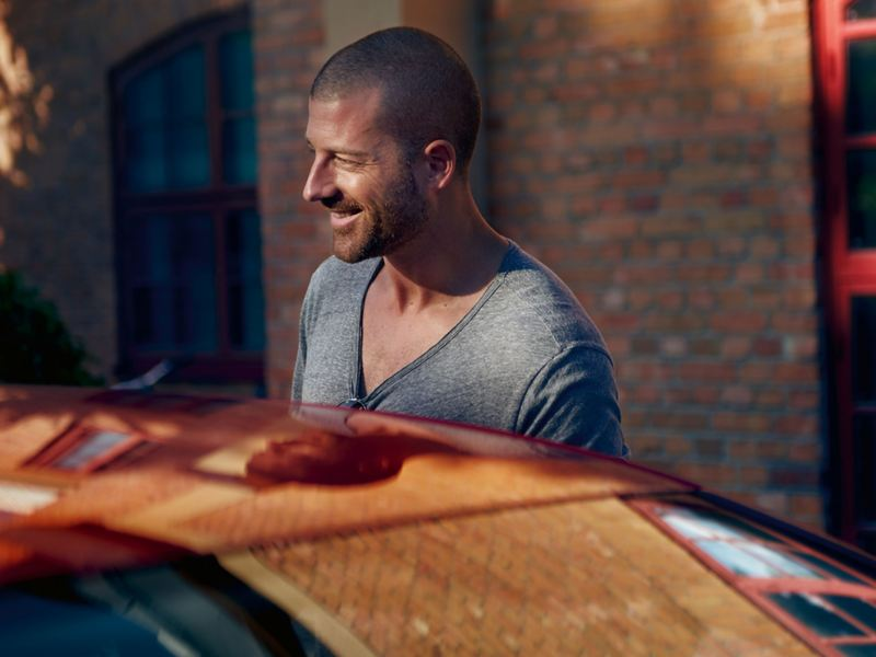 A smiling man standing behind a car