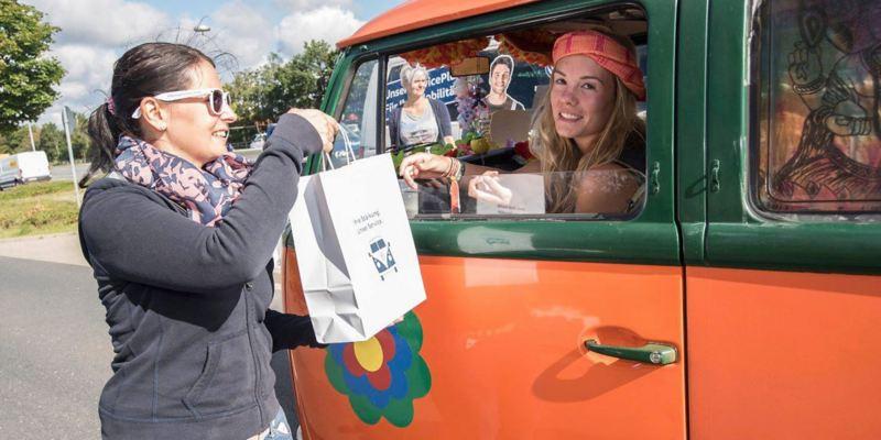 Eine Frau reicht Bulli-Fahrern eine Tüte mit Essen.