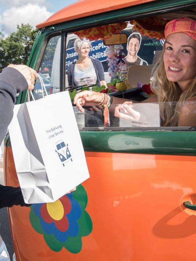 Uma senhora a entregar um saco com comida aos condutores das Pão de Forma.