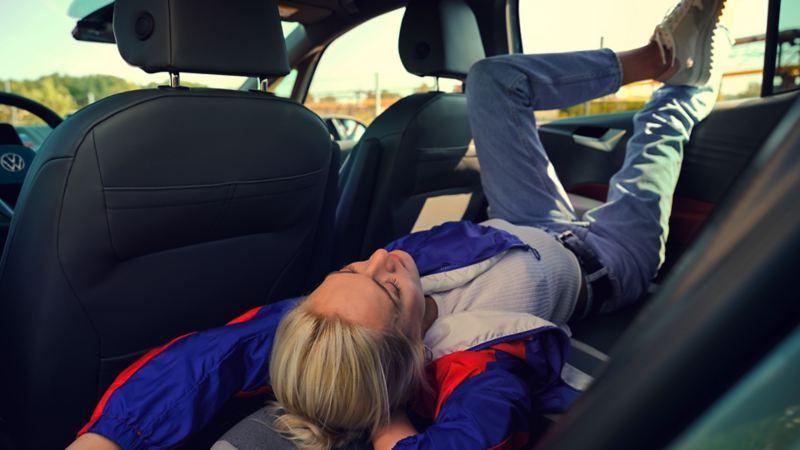 Eine junge Frau liegt entspannt auf der Rückbank des ID.3