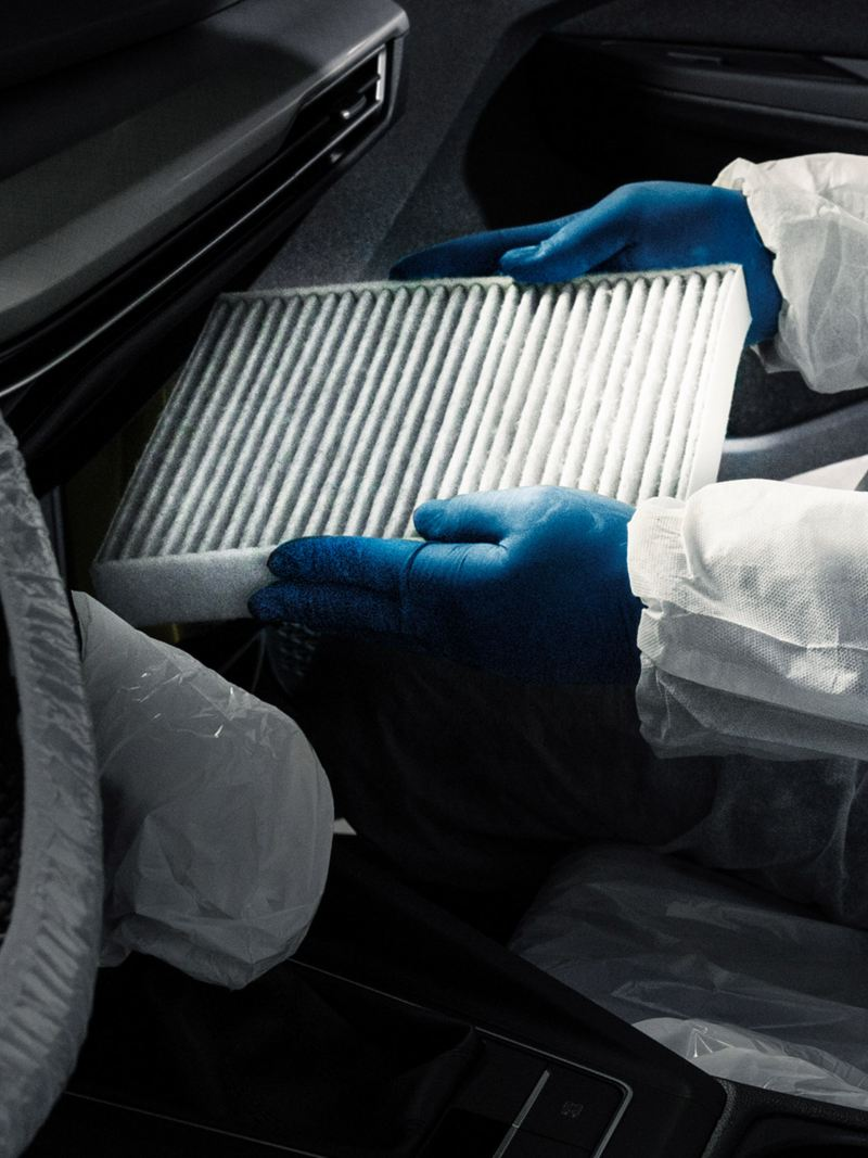 Un tecnico di Volkswagen Cervice mentre sostituisce il filtro antipolvere a antipolline di un'auto.