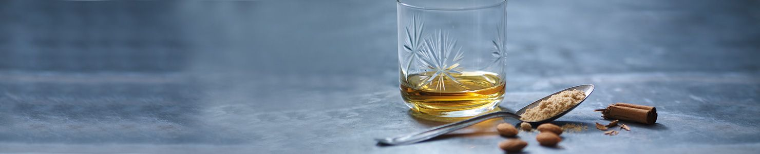 A dram of whisky in a glass tumbler